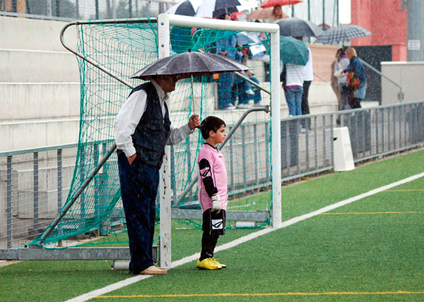 Un padre con el paraguas protege a su hijo portero mientras juega